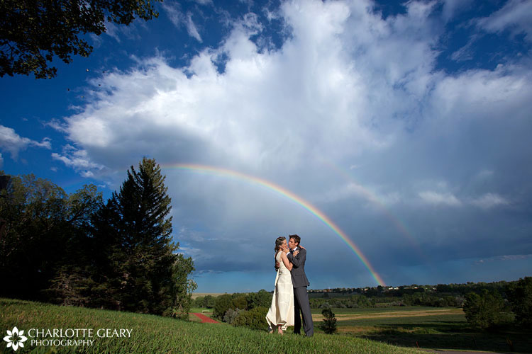 Bride and groom under a double rainbow | Photo by Charlotte Geary