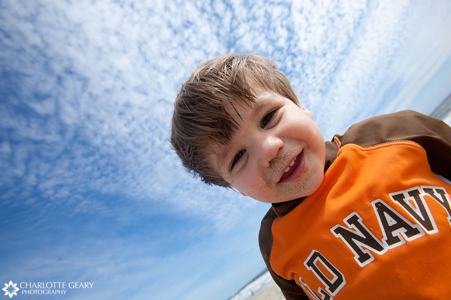 Toddler boy covered in sand in Corolla, NC | Photo by Charlotte Geary