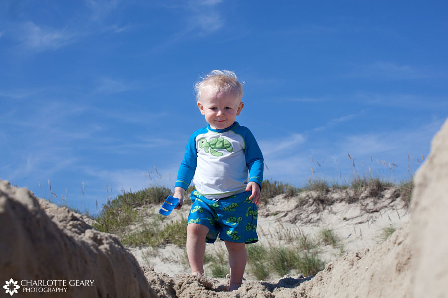Toddler boy playing in the sand in Corolla, NC | Photo by Charlotte Geary