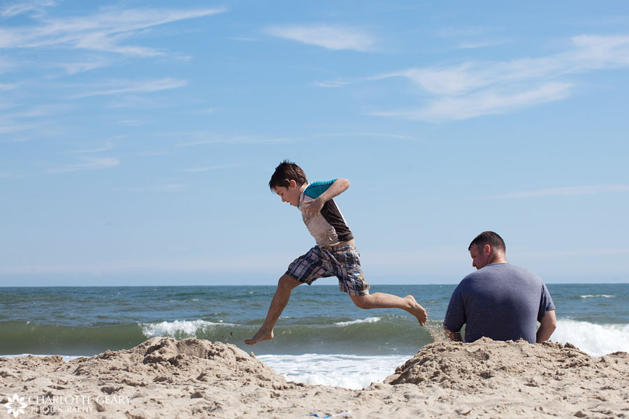 Boy jumping in the sand at the beach in Corolla, NC | Photo by Charlotte Geary
