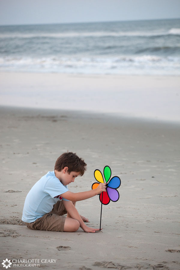 Boy playing with pinwheel at the beach