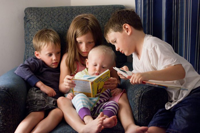 Documentary family photography of kids reading to a baby