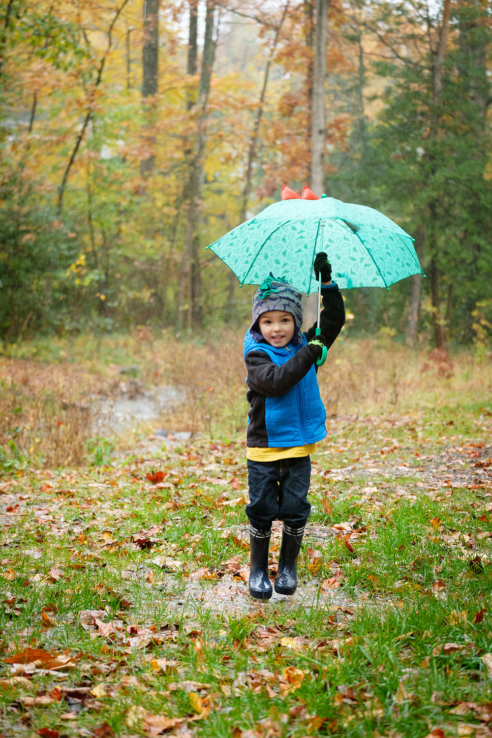Boy with umbrella playing in the rain