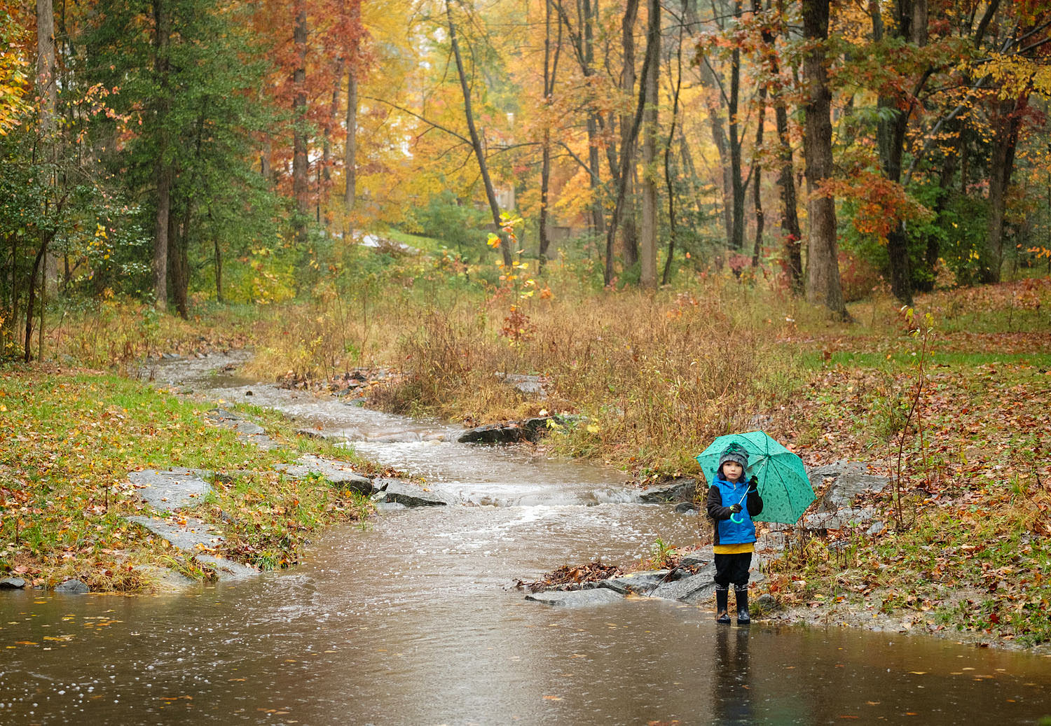 Boy playing in the rain at a stream