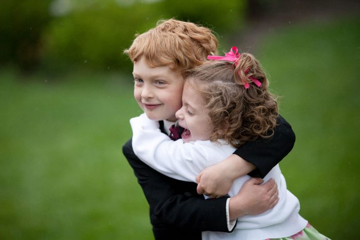 Ring bearer and flower girl hugging