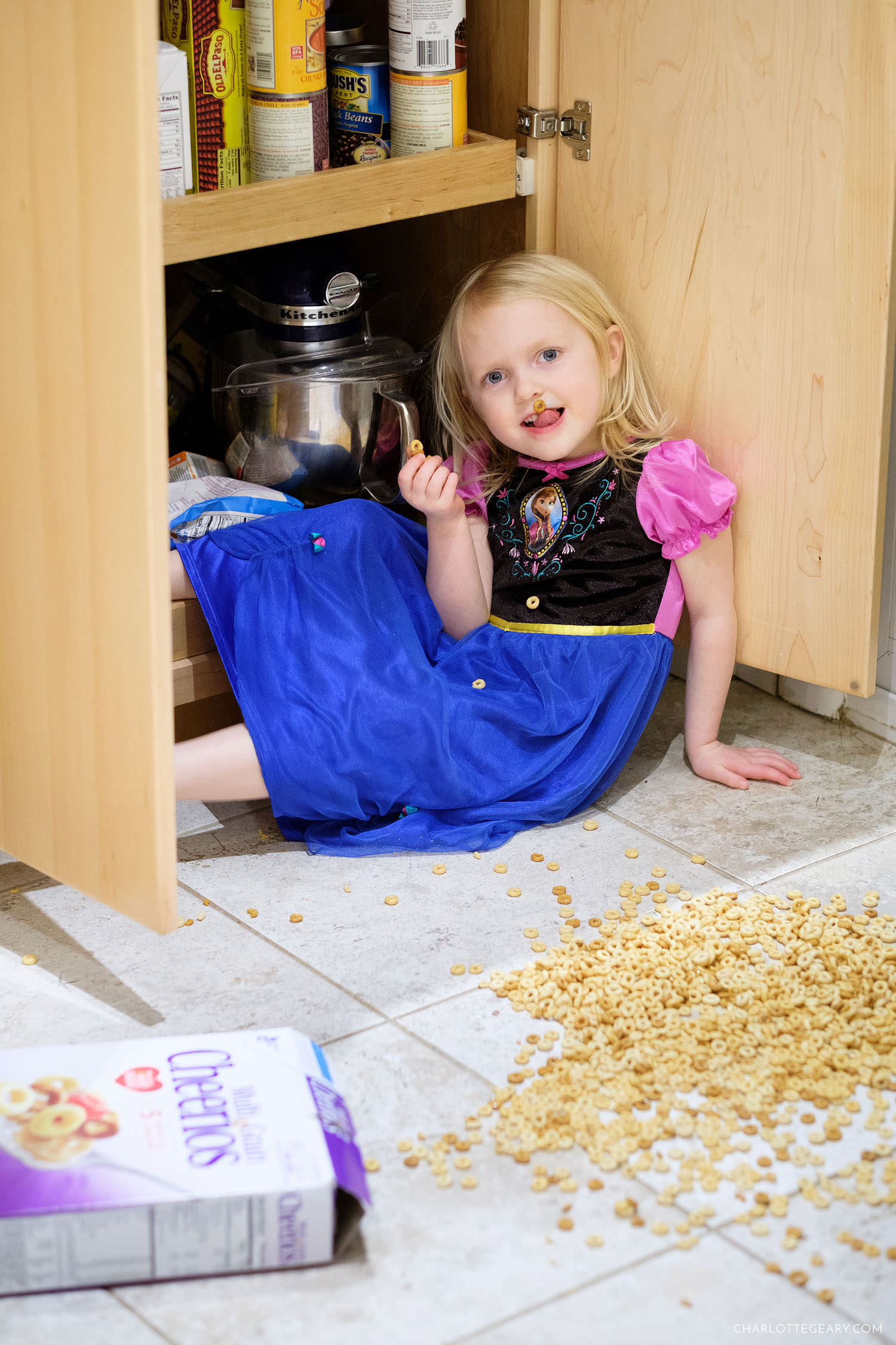 Little girl eats Cheerios off the floor